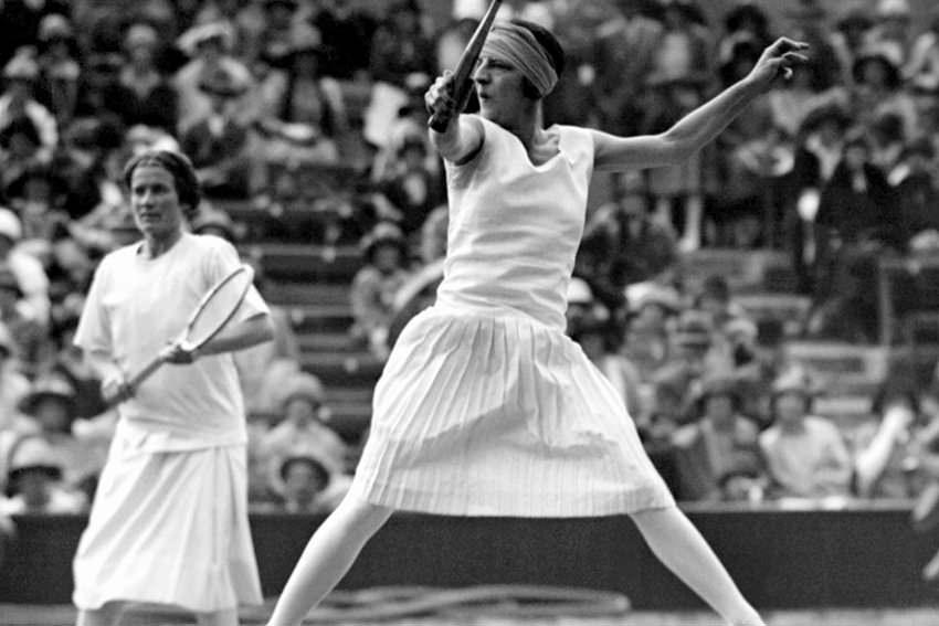 Die legendäre französische Tennisspielerin Suzanne Lenglen (1899-1938) am 17. Juni 1920 in einem Doppel-Match in Wimbledon. Zwischen 1919 und 1926 konnte sie sechs Mal das Wimbledon-Finale für sich entscheiden. Wie in der damaligen Zeit  üblich trug sie ein knielanges weißes Tenniskleid - heute modisch nicht mehr vorstellbar bei den knappen Röckchen der Damen Hingis, Kurnikowa oder Williams, aber auch sportlich  - wegen der schnellen, athletischen Spielweise - nicht mehr praktikabel. |
